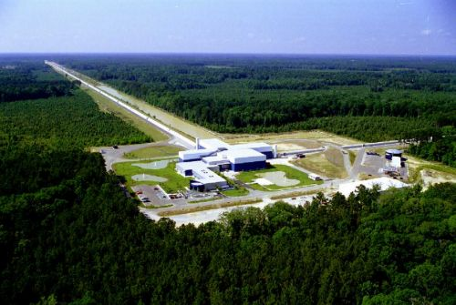 An aerial view of the LIGO instrument in Louisiana. This picture shows the central building, which contains the laser, the semi-silvered mirror, and the detector. We can see the large concrete tubes going out in two directions from the center, which encase the arms securely in large vacuum tubes; one goes off to the right, while the other extends to the top left of the picture. Each arm of the interferometer is 4 kilometers (about 2.4 miles) long.